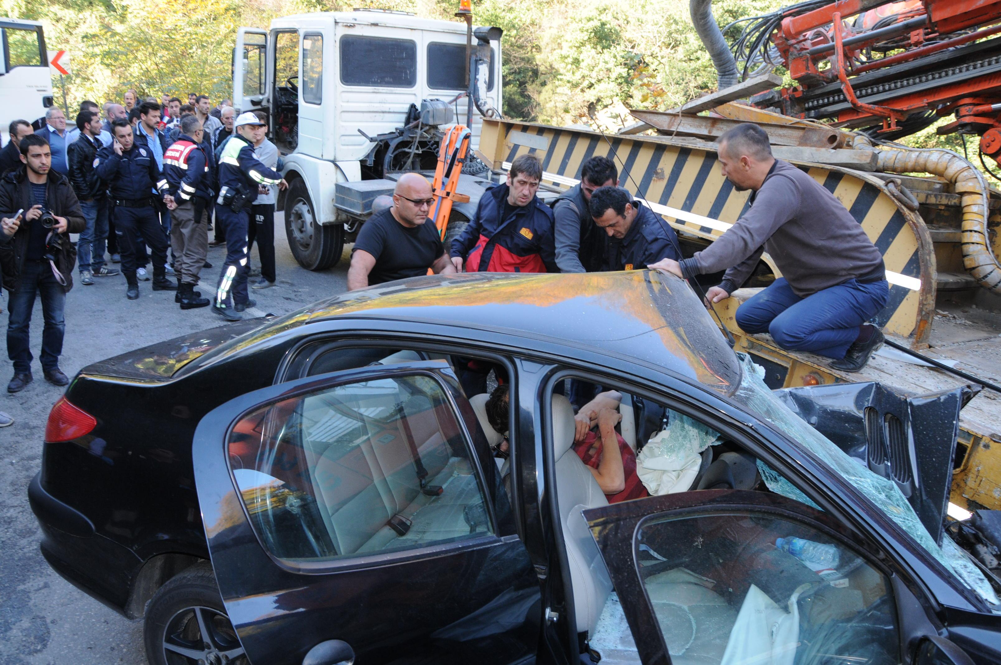 Zonguldak'ta, tırın dorse kısmının altına giren otomobilde sıkışan sürücü, bir saatlik çalışmayla çıkartıldı. ( Selim Bostancı - Anadolu Ajansı )